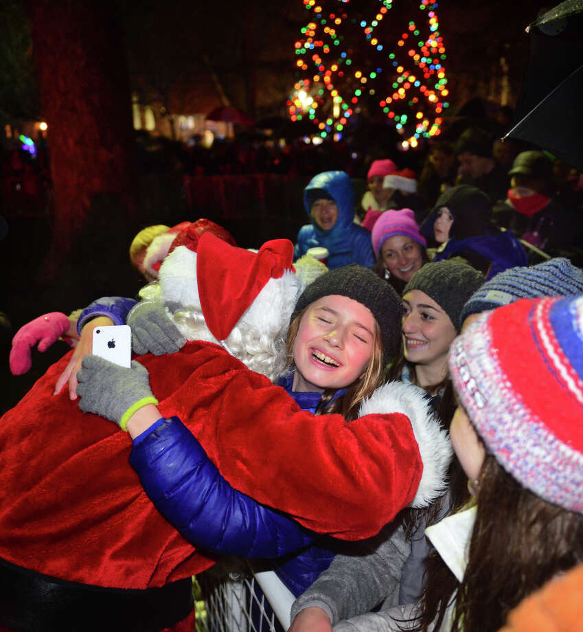 Emma Davies gives Santa Claus a big hug after his arrival at the Fairfield Town Hall Green after the annual tree lighting on Friday Dec. 5, 2014. Instead of snow, rain fell during the event this year, but it wasn't able to put a damper on things. Hundreds of families still gathered to listen to traditional Christmas songs performed by choirs from Roger Ludlowe Middle School and Fairfield Warde High School. Hot chocolate and snacks were sold by volunteers at St. Paul's Episcopal Church. Photo: Christian Abraham / Connecticut Post