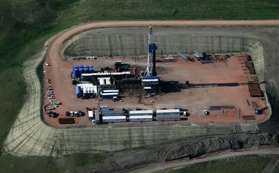 An oil well is drilled near Williston, N.D. A decision by OPEC not to cut oil production has prompted Barclays to cut its projection of 2015's average U.S. price of crude by $19 — from $84 to $66 per barrel. Photo: Charles Rex Arbogast, STF / Associated Press / AP