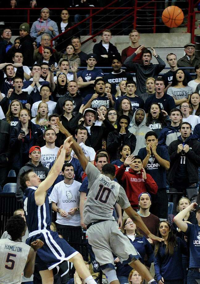 Yale's Jack Montague (4) shoots a game winning three-point shot while being guarded by Connecticut's Sam Cassell Jr. (10) during the second half of Yale's 45-44 upset victory in an NCAA college basketball game in Storrs, Conn., on Sunday, Dec. 5, 2014. Photo: Fred Beckham, AP / Associated Press