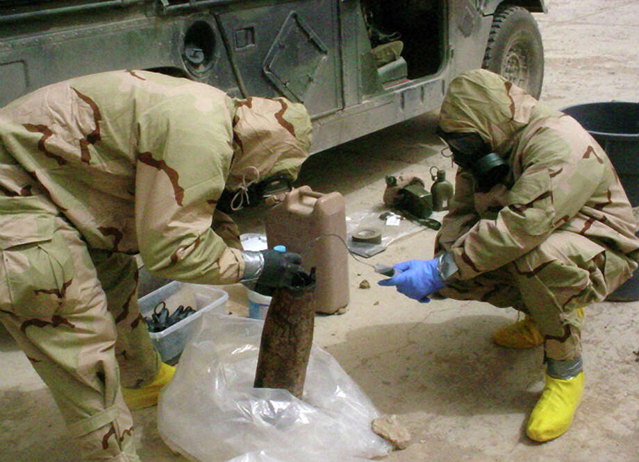 Soldiers siphon sarin from an artillery shell used as a makeshift bomb designed to disperse a nerve agent. Photo: THE NEW YORK TIMES / New York Times / THE NEW YORK TIMES