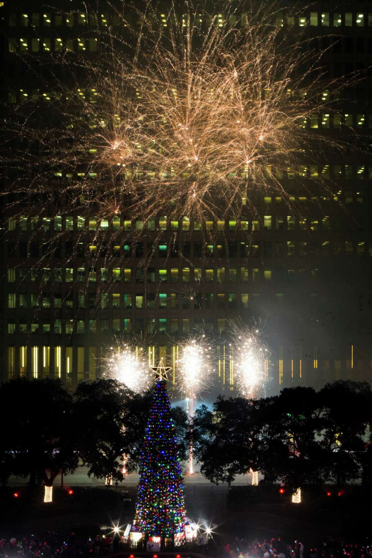 Fireworks put on a show behind the Christmas tree of Houston City Hall on Friday.