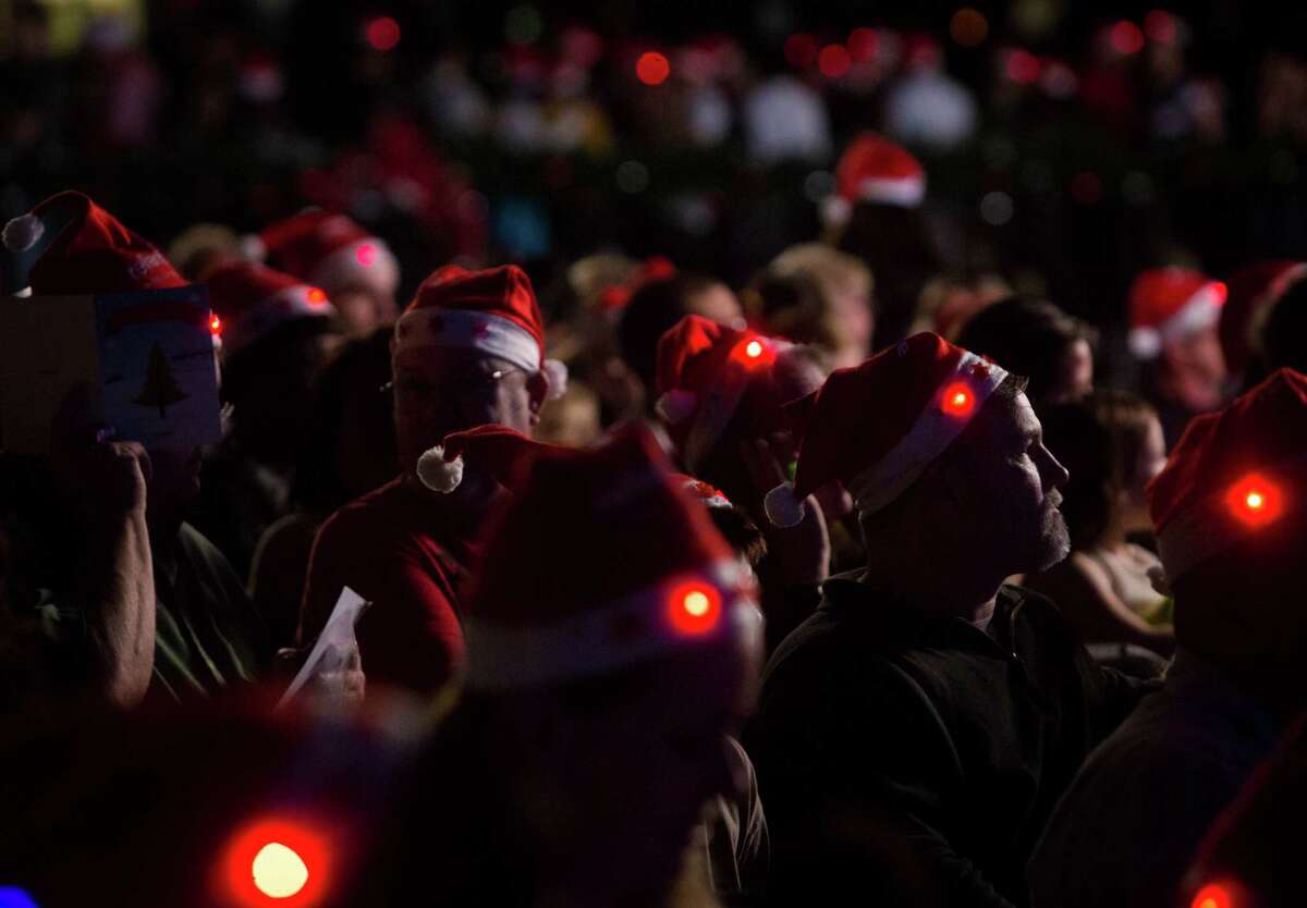 The crowd wears Santa Claus hats at the celebration.