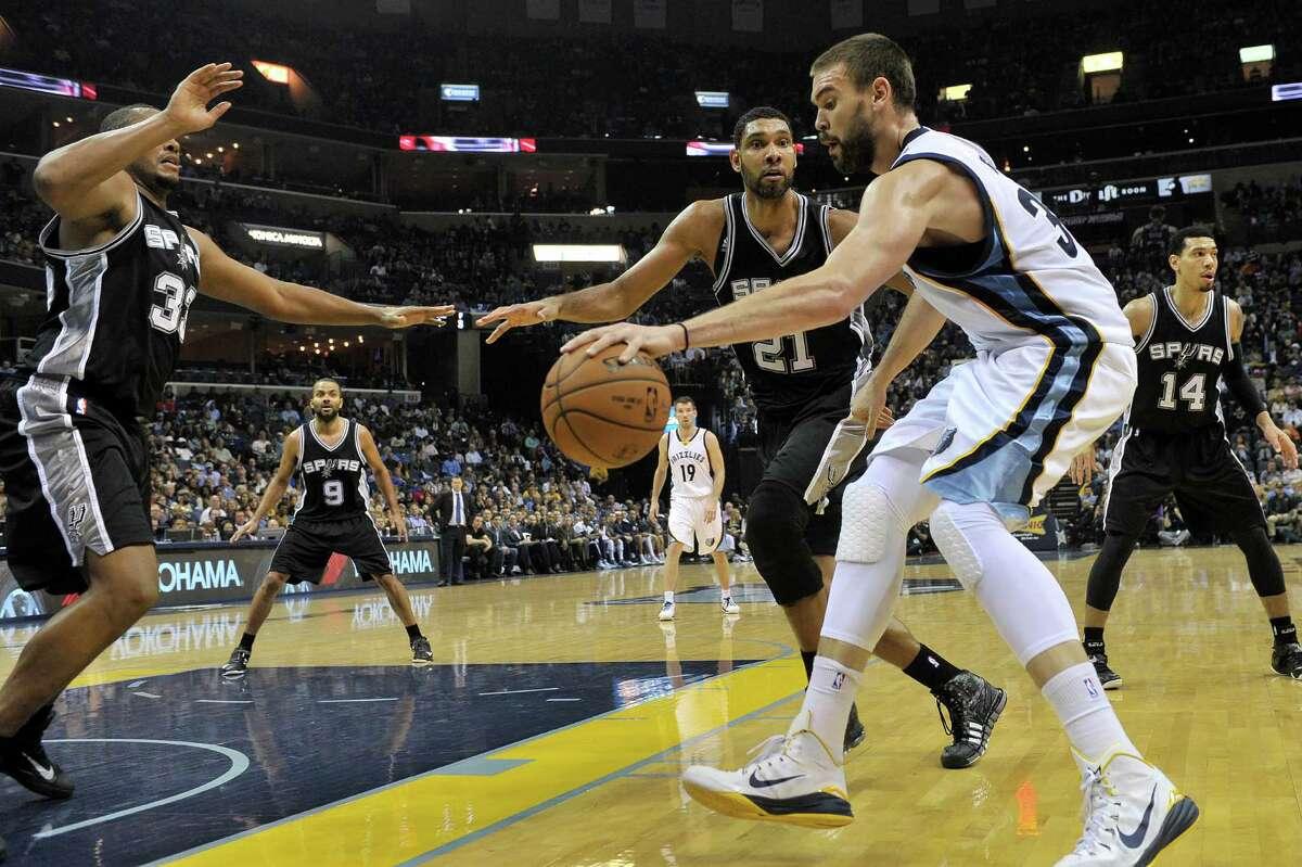 Memphis Grizzlies center Marc Gasol, right, drives toward the basket against San Antonio Spurs forward Boris Diaw, left, and forward Tim Duncan (21) in the first half of an NBA basketball game Friday, Dec. 5, 2014, in Memphis, Tenn.