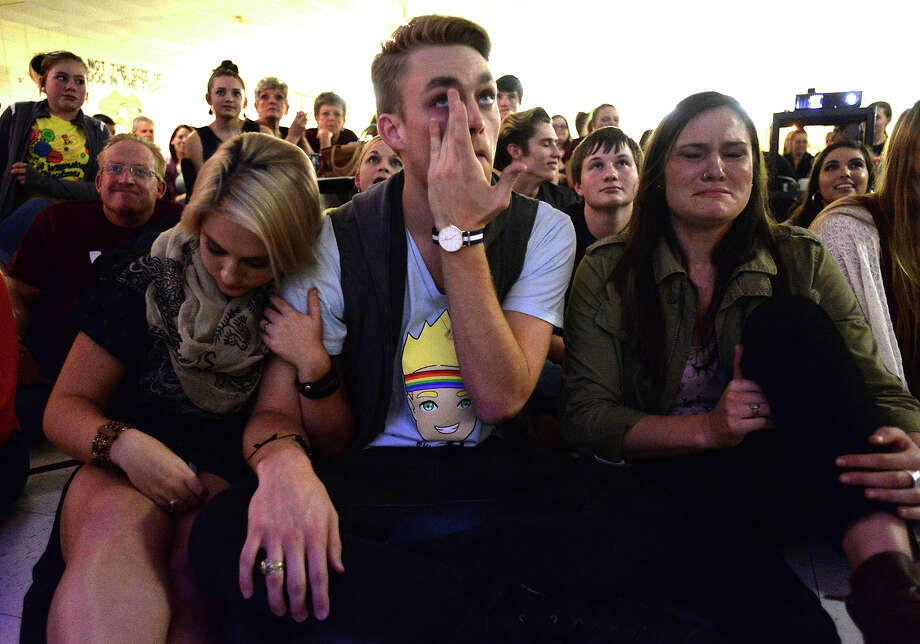 Surrounded by close friends, including Jenni Weeks (left) and Elizabeth Itz, Will Jardell of Nederland reacts after being eliminated in the final round while taking in the finale of America's Next Top Model at Nederland High School Friday. his season was the first to combine male and female contestants, Jardell among them. Photo taken Friday, December 5, 2014 Kim Brent/The Enterprise Photo: KIM BRENT / Beaumont Enterprise
