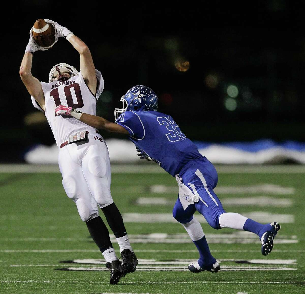 Hallaettsville receiver Trenton McGee #10 completes a pass over Edna's Jordan Norman #32 during a Class 4A Division II Region IV high school playoff game between Edna and Hallettsville on Friday, December 5, 2014. (Bob Levey/For The Chronicle)