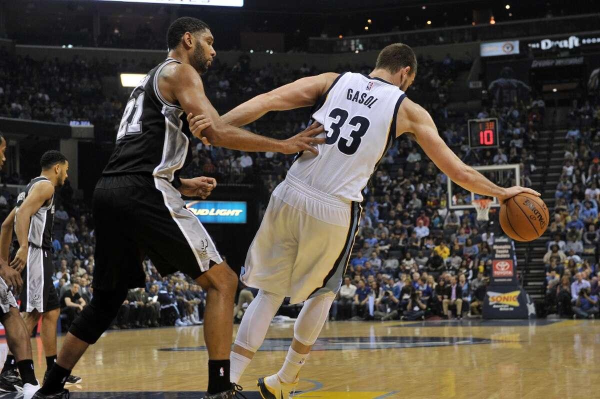 San Antonio Spurs forward Tim Duncan (21) defends against Memphis Grizzlies center Marc Gasol (33) in the first half of an NBA basketball game Friday, Dec. 5, 2014, in Memphis, Tenn. (AP Photo/Brandon Dill)