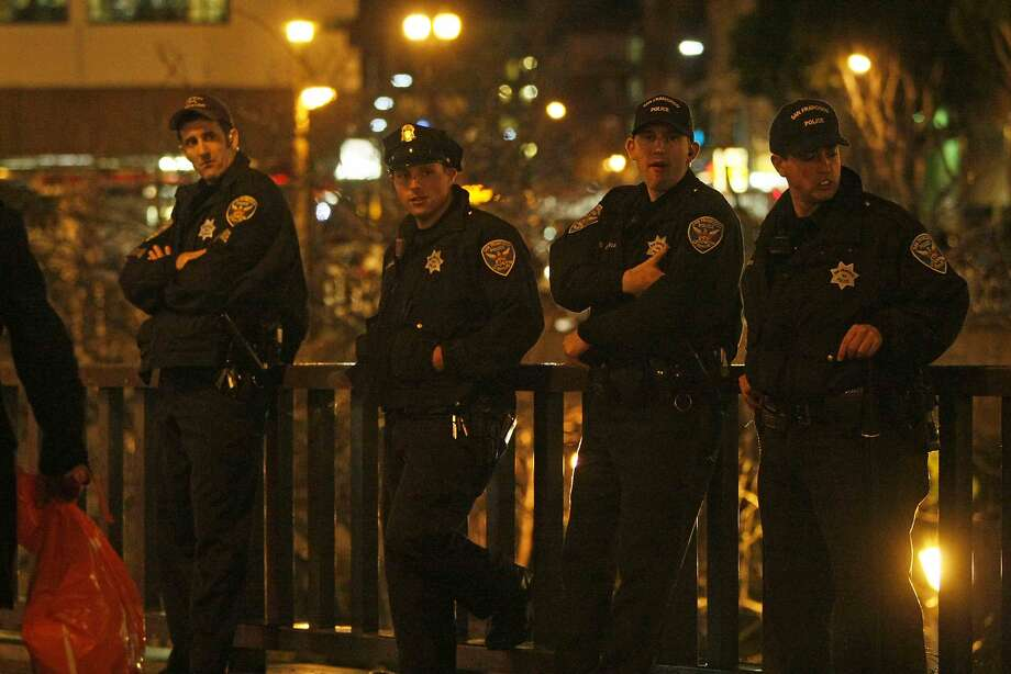 Police stand by at Powell and Market streets before a protest in San Francisco, Calif. Friday, December 5, 2014 against the shooting of Michael Brown in Ferguson, Missouri and the chokehold death of Eric Garner in New York City Photo: Jessica Christian, The Chronicle