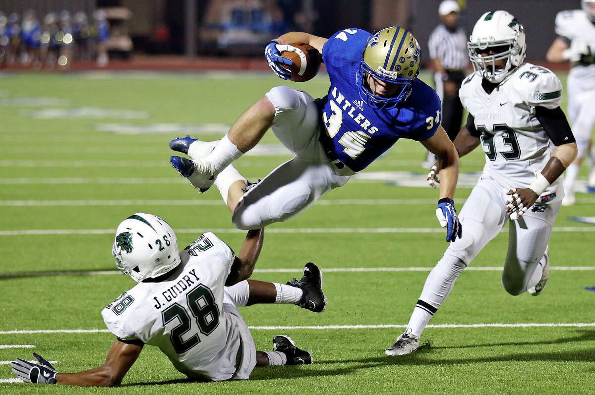 Kerrville Tivy's Hayden Schreckenbach(34) looks for room over Cedar Park's Jav Guidry during first half action of their Class 5A Division II state quarterfinal playoff game on Dec. 5, 2014 at Alamo Stadium.
