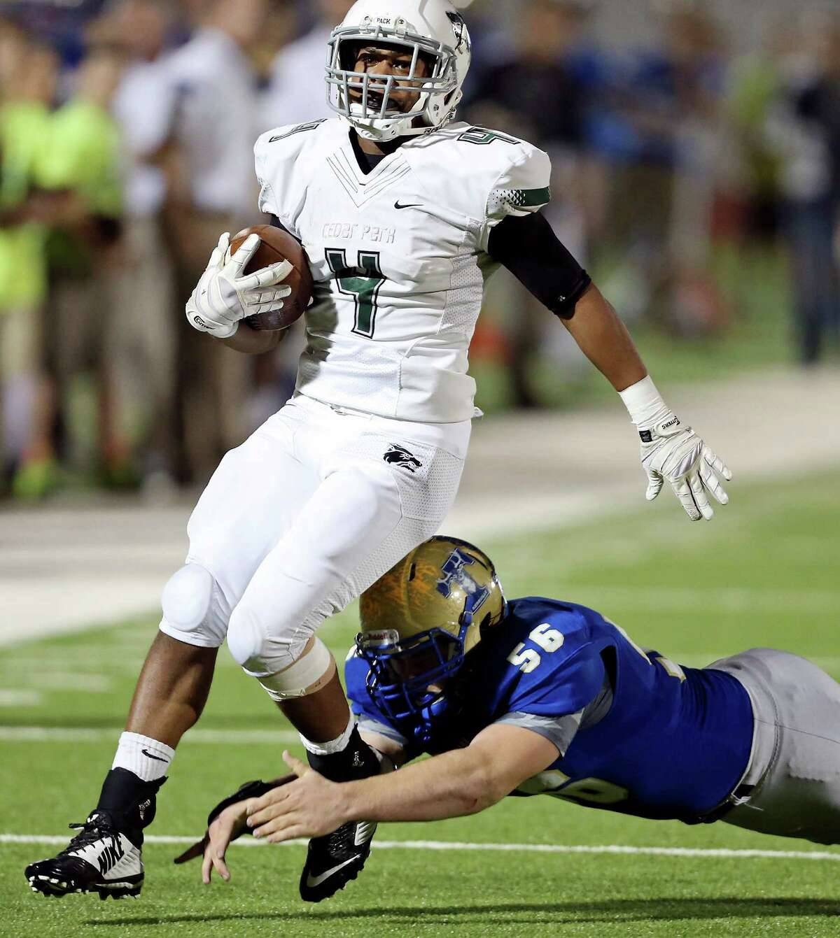 Cedar Park's Chris Hutchings tries to shake the tackle of Kerrville Tivy's Ronan Profeta during first half action of their Class 5A Division II state quarterfinal playoff game Friday Dec. 5, 2014 at Alamo Stadium.
