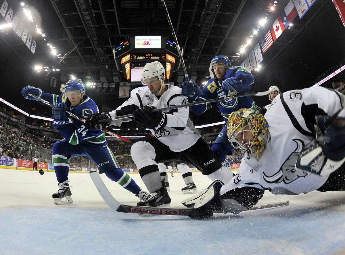 San Antonio Rampage goaltender Dan Ellis, right, makes a save on Utica Comets' Carter Bancks (34) during the first period of an AHL hockey game between the Utica Comets and the San Antonio Rampage, Friday, Dec. 5, 2014, in San Antonio.