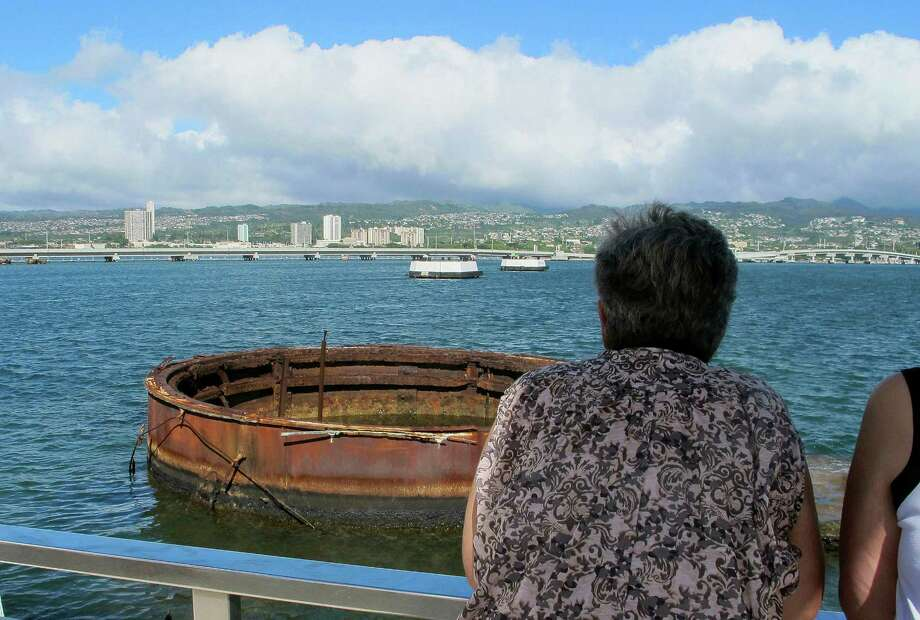 This Nov. 21, 2014 photo shows visitors looking out at the sunken USS Arizona from a memorial atop the rusting battleship in Pearl Harbor, Hawaii. The USS Arizona is one of the nation's most hallowed sites, an underwater grave for more than 900 sailors and Marines killed when Japan bombed Pearl Harbor and sank their ship in 1941, but it's now the scene of alleged rampant mismanagement. (AP Photo/Audrey McAvoy) Photo: Audrey McAvoy, STF / Associated Press / AP