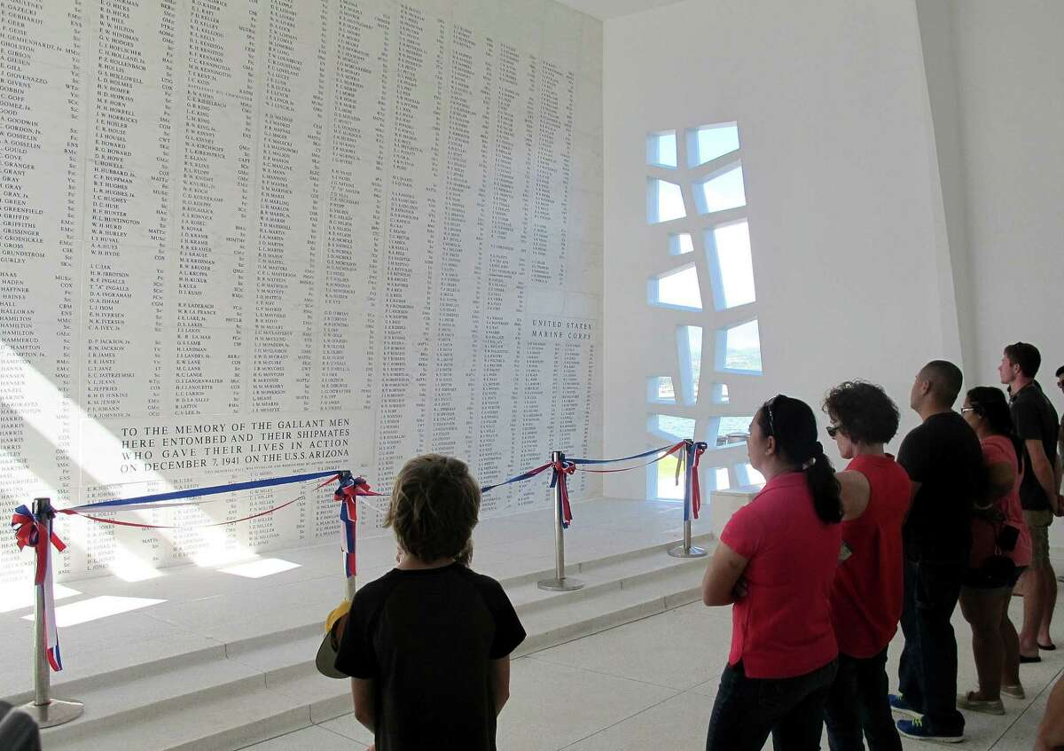 This Nov. 21, 2014 photo shows visitors looking at a wall inscribed with the names of the USS Arizona's fallen at a memorial for the sunken battleship in Pearl Harbor, Hawaii. The USS Arizona is one of the nation's most hallowed sites, an underwater grave for more than 900 sailors and Marines killed when Japan bombed Pearl Harbor and sank their ship in 1941, but it's now the scene of alleged rampant mismanagement. (AP Photo/Audrey McAvoy)
