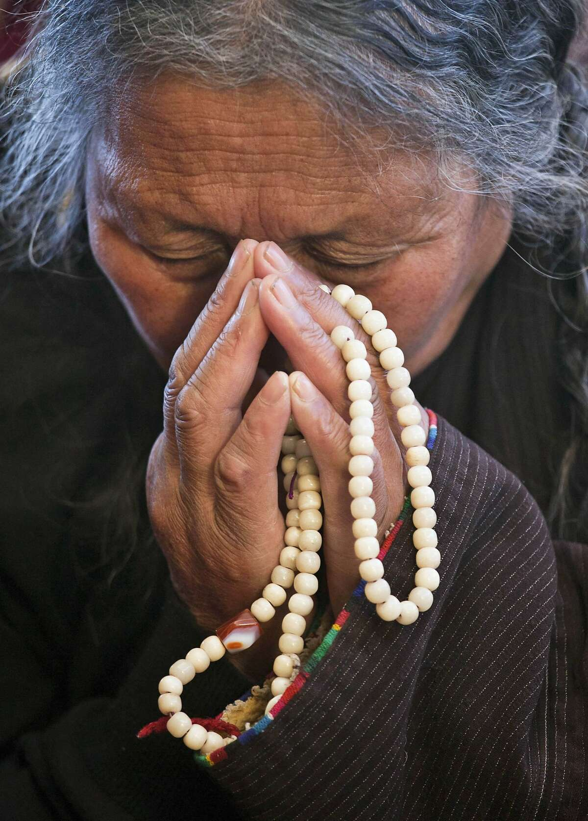 An exile Tibetan prays as she listens to a talk by spiritual leader the Dalai Lama at the Tsuglakhang temple in Dharmsala, India, Friday, Dec. 5, 2014. The four-day talk for a Mongolian Buddhist group ended Friday. (AP Photo/Ashwini Bhatia)