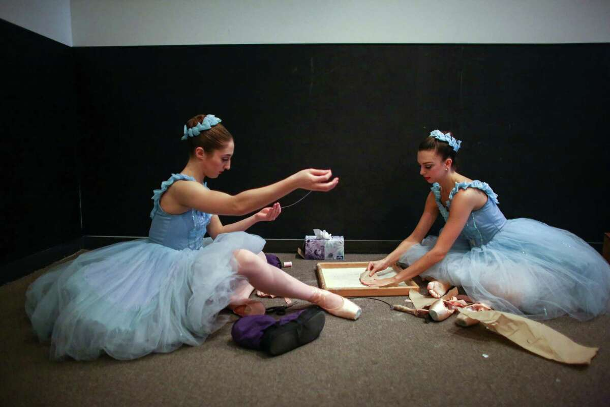 PNB apprentice Nicole Rizzitano, left, and corps de ballet dancer Amanda Clark ready their feet and shoes for the snow scene during one of the final performances of Pacific Northwest Ballet's popular Nutcracker.