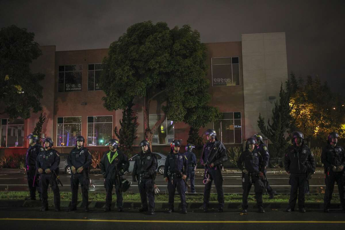 Policemen line up during protests in Oakland, December 5, 2014 in response to the shooting of Michael Brown and the death of Eric Garner.