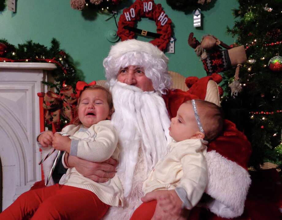 Cousins Avellina Progano and Francesca Naccarato had different reactions to their visit with Santa Claus at the Burr Homestead Friday at the 34th annual Fairfield Christmas Tree Festival. Avellina, 18 months, of Fairfield, was frightened of the man in red -- although she hugged a plush Santa on display in another room -- while Francesca, 7  months, of Buffalo, N.Y., was mesmerized by her first visit with Santa. Photo: Meg Barone / Fairfield Citizen