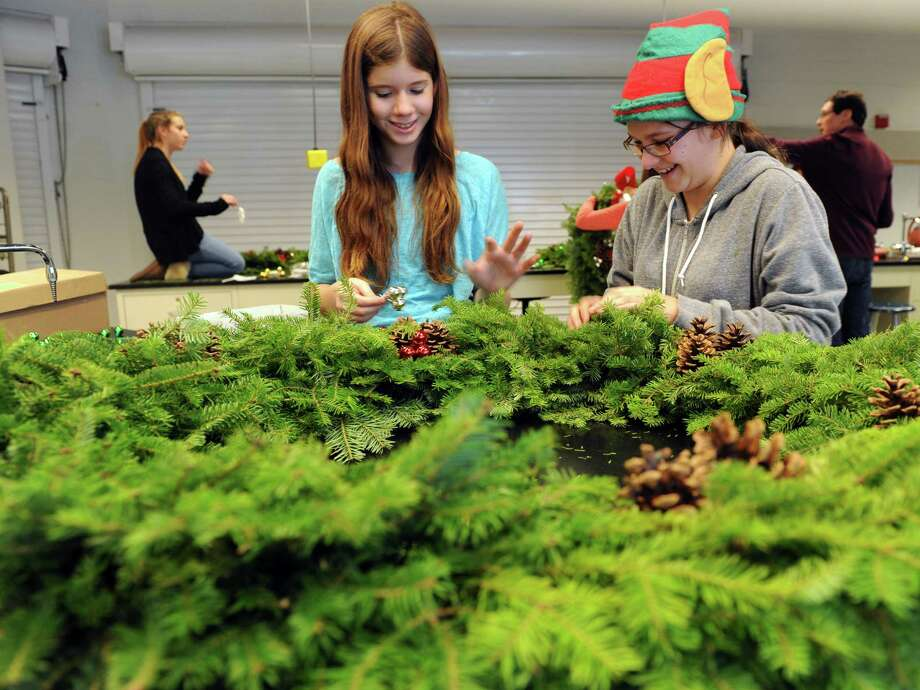 Freshmen Jordan Reda, 14, of Trumbull, left, and Makayla Albert, 14, of Stratford, decorate wreaths Saturday, Dec. 6, 2014, during the Holiday Craft Fair and Plant Sale at the Trumbull Agriscience Center at Trumbull High School. The event which continues Sunday from 10 a.m. to 4 p.m., showcases a variety of arts and craft vendors from the local area as well as holiday plants and wreaths grown by the students in the Agriscience greenhouses. Photo: Autumn Driscoll / Connecticut Post