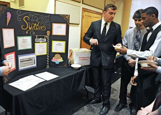 Sophomore Michael Orso of Catskill, left, gives a sample of ice cream to freshman Tyriek McGraw of Albany, right, from his team's business Sundaes on Broadway as teams of students from The College of Saint Rose offer presentations on what kinds of businesses downtown Albany needs at the Saint Joseph Hall Auditorium on Wednesday, Nov. 3, 2014 in Albany, N.Y. (Lori Van Buren / Times Union) Photo: Lori Van Buren / 00029685A