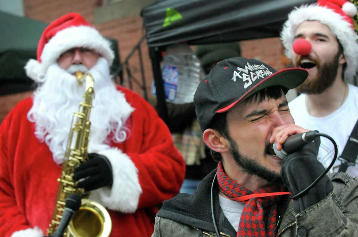 Jon DeLong lead singer of the band Nine Votes Short is accompanied on a song by Sax-O-Claus, Luke McNamee, and guitarist Dalton Lyons during the 2014 Santa Speedo Sprint in conjunction with Winter Wonderlark on Saturday Dec. 6, 2014 in Albany, N.Y. (Michael P. Farrell/Times Union)