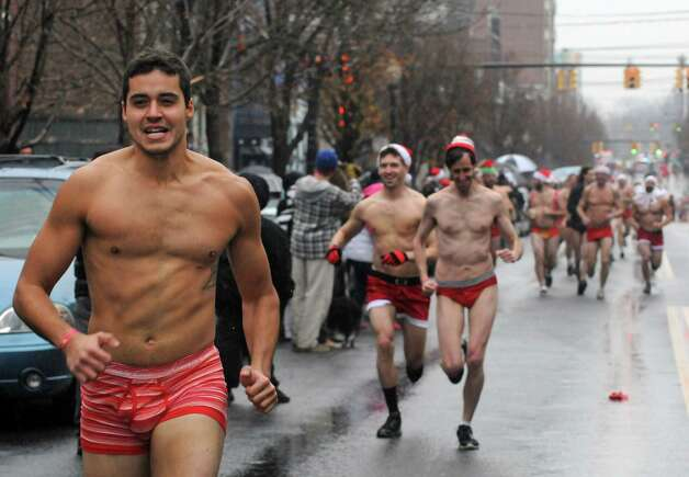 Felipe Cavalcanti, left, of Albany was the first men's finisher in the 2014 Santa Speedo Sprint in conjunction with Winter Wonderlark on Saturday Dec. 6, 2014 in Albany, N.Y.  (Michael P. Farrell/Times Union) Photo: Michael P. Farrell / 00029715A