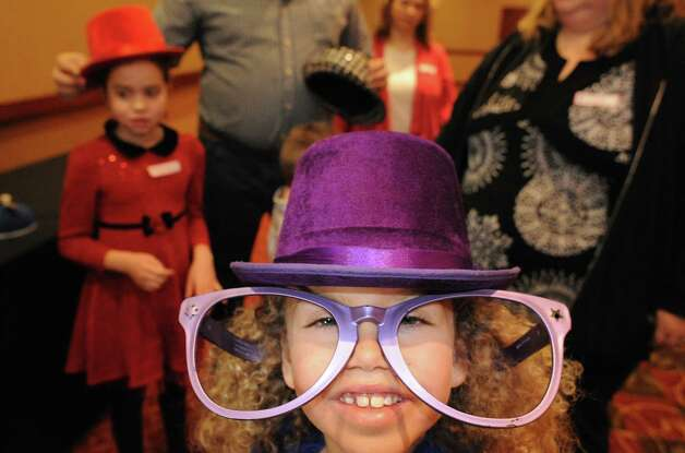 Seven-year-old Miracle Carter dresses in a top hat and large glasses before she enter a photo booth during the YMCA's Circle of Champs Holiday Party at the Hilton Garden Inn on Saturday Dec. 6, 2014 in Troy, N.Y.  Children and families battling life-threatening illnesses gather to enjoy holiday festivities at the annual Holiday Party for the Capital District YMCA Circle of Champs program.The Circle of Champs program brings joy into the lives of children fighting cancer and other life-threatening illnesses, as well as respite for their brothers, sisters and parents.(Michael P. Farrell/Times Union) Photo: Michael P. Farrell / 00029767A