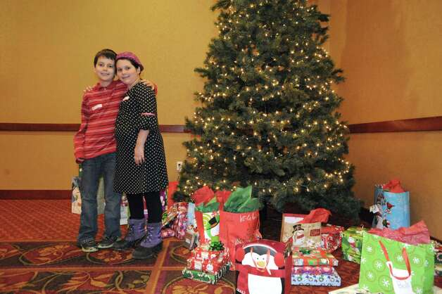 Eleven-year-old Ryan LeVeille with his nine-year-old sister Emily LeVeille pose in front of the Christmas tree during the YMCA's Circle of Champs Holiday Party at the Hilton Garden Inn on Saturday Dec. 6, 2014 in Troy, N.Y.  (Michael P. Farrell/Times Union) Photo: Michael P. Farrell / 00029767A