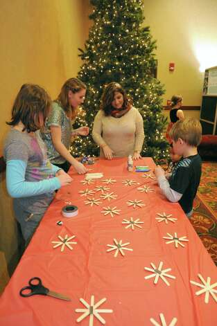 YMCA employees Heather Coffey, left, and Stephanie Klein, center, help children make snow flake ornaments during the YMCA's Circle of Champs Holiday Party at the Hilton Garden Inn on Saturday Dec. 6, 2014 in Troy, N.Y.  (Michael P. Farrell/Times Union) Photo: Michael P. Farrell / 00029767A