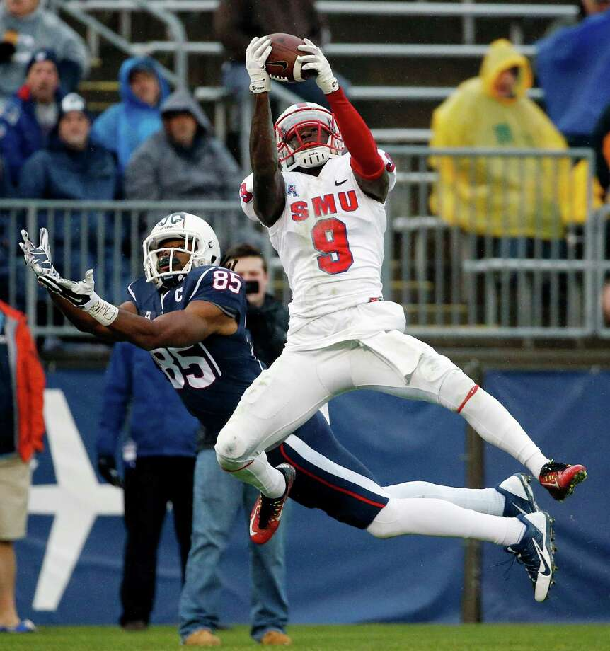 SMU defensive back Horace Richardson (9) intercepts the pass intended for Connecticut wide receiver Geremy Davis (85) during the second quarter of an NCAA college football game in East Hartford, Conn., Saturday, Dec. 6, 2014. Photo: Michael Dwyer, AP / Associated Press