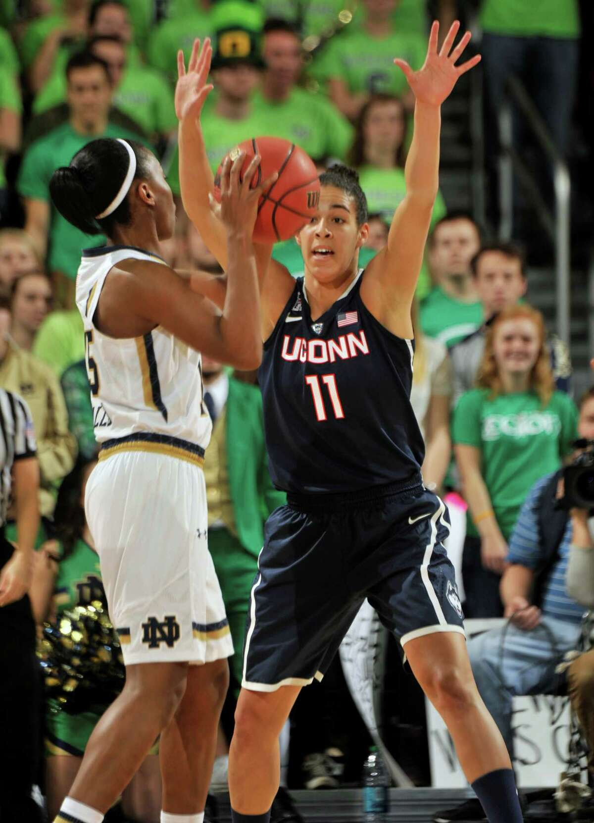 Notre Dame guard Lindsay Allen, left, throws a pass around Connecticut guard Kia Nurse in the first half of an NCAA college basketball game, Saturday Dec. 6, 2014, in South Bend, Ind.