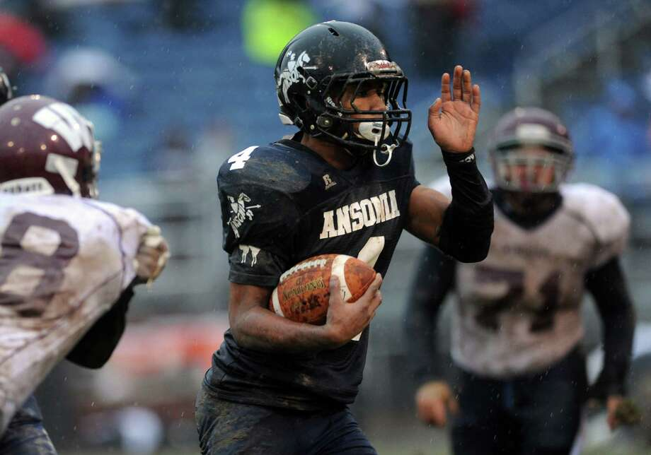 Ansonia's Tajik Bagley carries the ball between two Windham defensive players Saturday, Dec. 6, 2014, during the CIAC Class S Large Division semifinals at Nolan Field in Ansonia, Conn. Photo: Autumn Driscoll / Connecticut Post