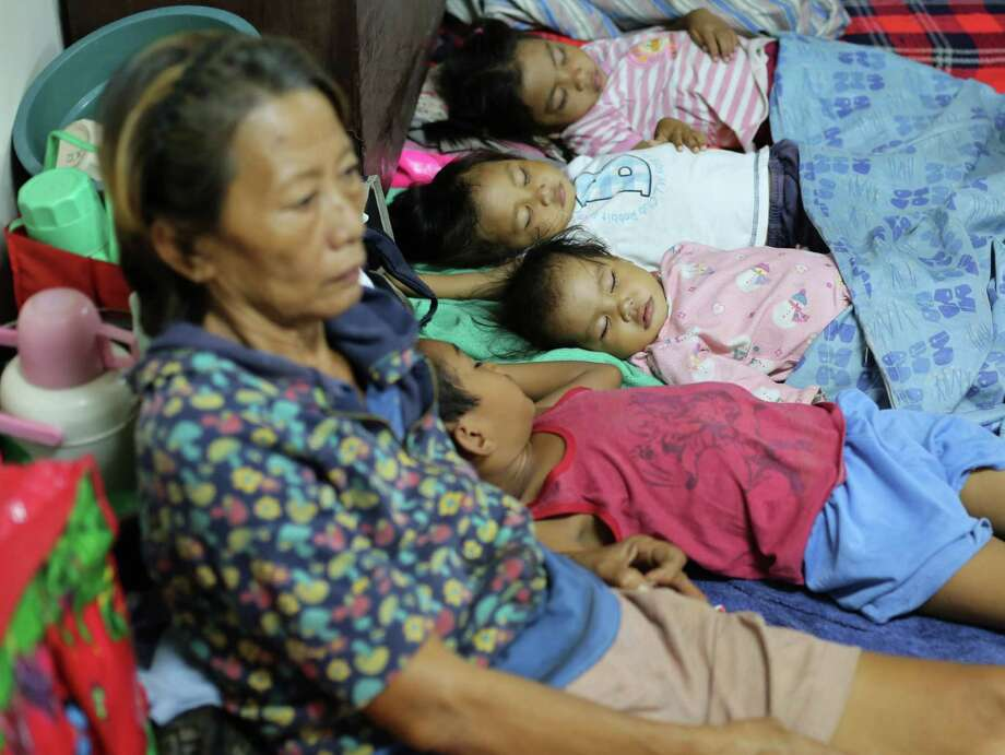Filipino children sleep as families seek refuge at a school used as an evacuation center as they prepare for Typhoon Hagupit in Legazpi, Albay province, eastern Philippines, Saturday, Dec. 6, 2014. Typhoon Hagupit slammed into the central Philippines' east coast late Saturday, knocking out power and toppling trees in a region where 650,000 people have fled to safety, still haunted by the massive death and destruction wrought by a monster storm last year. (AP Photo/Aaron Favila) ORG XMIT: XAF107 Photo: Aaron Favila / AP