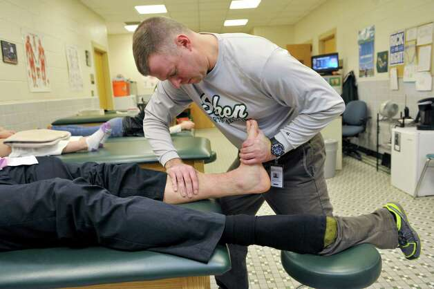 Shenendehowa High School athletic trainer Rick Knizek works on the ankle of student athlete Brandon Fischer Wednesday, Dec. 3, 2014, at the school's in-house training room in Clifton Park, N.Y.   (Paul Buckowski / Times Union) Photo: Paul Buckowski / 00029720A