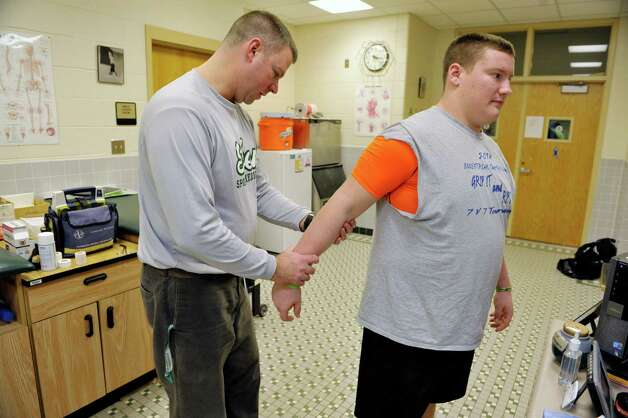Shenendehowa High School athletic trainer Rick Knizek looks over the elbow of football player Dan Busold Wednesday, Dec. 3, 2014, at the school's in-house training room in Clifton Park, N.Y.   (Paul Buckowski / Times Union) Photo: Paul Buckowski / 00029720A