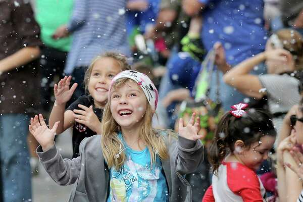 From to back, Maddie Wissel, age 5, from League City and Zoey Rodriguez, age 5, from Pearland play with the fallen artificial snow as the parade marches by on Dickens on the Strand on Saturday, December 6, 2014 in Galveston, TX.