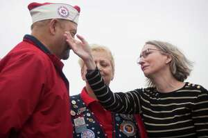 Lori LaGesse, right, extends her arm to dry the tears of Jeff Smith, left, during the Pearl Harbor Memorial Ceremony at the Battleship Texas in La Porte, Saturday, Dec. 6, 2014. Both of them are mourning the loss of their fathers who passed away this year. Both fathers were Pearl Harbor survivors.