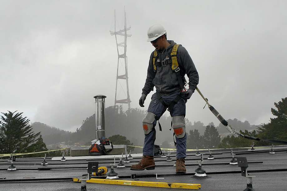 In this file photo, a crew lead Luis A. Hernandez from Luminalt works on racks on a roof for solar panels on a Twin Peaks home in San Francisco. Photo: Liz Hafalia, The Chronicle