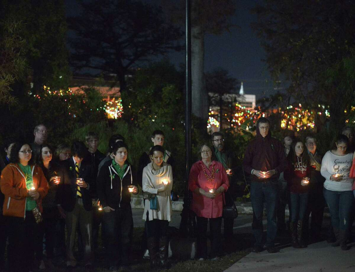 """People attend a one-year-anniversary candlelight vigil at Breckenridge Park for Cameron Redus, a University of the Incarnate Word student who was shot and killed by a campus policeman during an altercation at his off-campus apartment, on Dec. 6, 2014. The university's Christmas lights are visible in the background in this picture. The university on Friday announced changes that have been brought about as a result of the Redus shooting. These changes include a new police chief, enhancing communication for evening and weekend calls and more emphasis on """"community policing."""""""