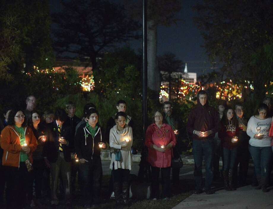 "People attend a one-year-anniversary candlelight vigil at Breckenridge Park for Cameron Redus, a University of the Incarnate Word student who was shot and killed by a campus policeman during an altercation at his off-campus apartment, on Dec. 6, 2014. The university's Christmas lights are visible in the background in this picture. The university on Friday announced changes that have been brought about as a result of the Redus shooting. These changes include a new police chief, enhancing communication for evening and weekend calls and more emphasis on ""community policing."" Photo: Billy Calzada, San Antonio Express-News / San Antonio Express-News"