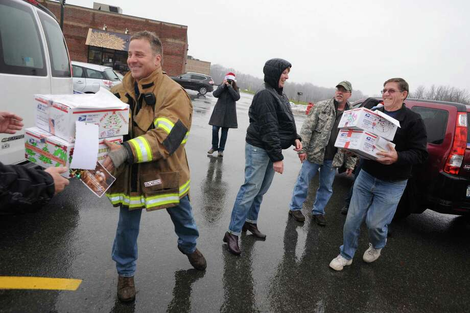 Elsmere Fire Company firefighter Marc Futia, left, helps load boxes of Christmas Cards to Our Troops on Saturday Dec. 6, 2014 in Glenmont, N.Y. This yeara€™s mailing will consist of approximately 55 boxes packed with 1,000 cards each. Prior to Saturdaya€™s mailing, 38 boxes have been mailed to various bases and carriers during the last three weeks. Christmas cards have been collected from all over the US from individuals, organizations, church groups, elementary schools, boy scout troops, girl scout troops and events. This year, eight McDonalda€™s locations in the capital district collected card and held events to collect cards for the boxes. Both Ronald McDonald and Santa Claus have attended the events.This is the fifth year for the mailing parade. Each year the number of cards has grown. What started as 2,000 the first year has now grown to over 100,000 cards in 2014. The boxes are mailed to bases in Afghanistan, Qatar, Kuwait, Italy, Japan, South Korea, Jordan, and UAE. (Michael P. Farrell/Times Union) Photo: Michael P. Farrell / 00029669A