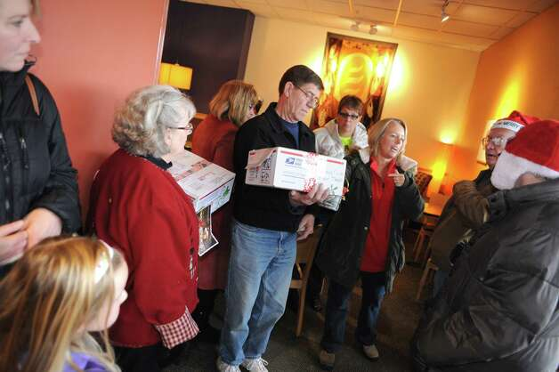 Organizer Melody D. Burns, right, instructs olunteers prior to loading boxes of Christmas Cards to Our Troops on Saturday Dec. 6, 2014 in Glenmont, N.Y. This yeara€™s mailing will consist of approximately 55 boxes packed with 1,000 cards each. Prior to Saturdaya€™s mailing, 38 boxes have been mailed to various bases and carriers during the last three weeks. Christmas cards have been collected from all over the US from individuals, organizations, church groups, elementary schools, boy scout troops, girl scout troops and events. This year, eight McDonalda€™s locations in the capital district collected card and held events to collect cards for the boxes. Both Ronald McDonald and Santa Claus have attended the events.This is the fifth year for the mailing parade. Each year the number of cards has grown. What started as 2,000 the first year has now grown to over 100,000 cards in 2014. The boxes are mailed to bases in Afghanistan, Qatar, Kuwait, Italy, Japan, South Korea, Jordan, and UAE. (Michael P. Farrell/Times Union) Photo: Michael P. Farrell / 00029669A