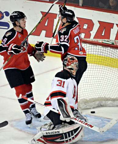 Portland Pirates' #32 Tyler Gaudet celebrates his goal with teammate #19 Henrik Samuelson, left, as Albany Devils goalie #31 Scott Wedgewood looks on during Saturday's game at the Times Union Center Dec. 6, 2014, in Albany, NY.   (John Carl D'Annibale / Times Union) Photo: John Carl D'Annibale / 00029286E