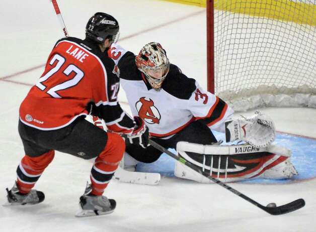 Albany Devils goalie Scott Wedgewood, right, stops a shot on goal by Portland Pirates' #22 Phil Lane during Saturday's game at the Times Union Center Dec. 6, 2014, in Albany, NY.   (John Carl D'Annibale / Times Union) Photo: John Carl D'Annibale / 00029286E