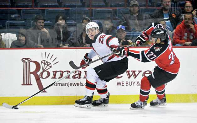 Albany Devils's #26 Ben Thomson, left, and Portland Pirates' #27 Evan Oberg during Saturday's game at the Times Union Center Dec. 6, 2014, in Albany, NY.   (John Carl D'Annibale / Times Union) Photo: John Carl D'Annibale / 00029286E