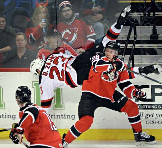 Albany Devils's #23 Darcy Zajac is upended by Portland Pirates' #28 Justin Hache during Saturday's game at the Times Union Center Dec. 6, 2014, in Albany, NY.   (John Carl D'Annibale / Times Union) Photo: John Carl D'Annibale / 00029286E