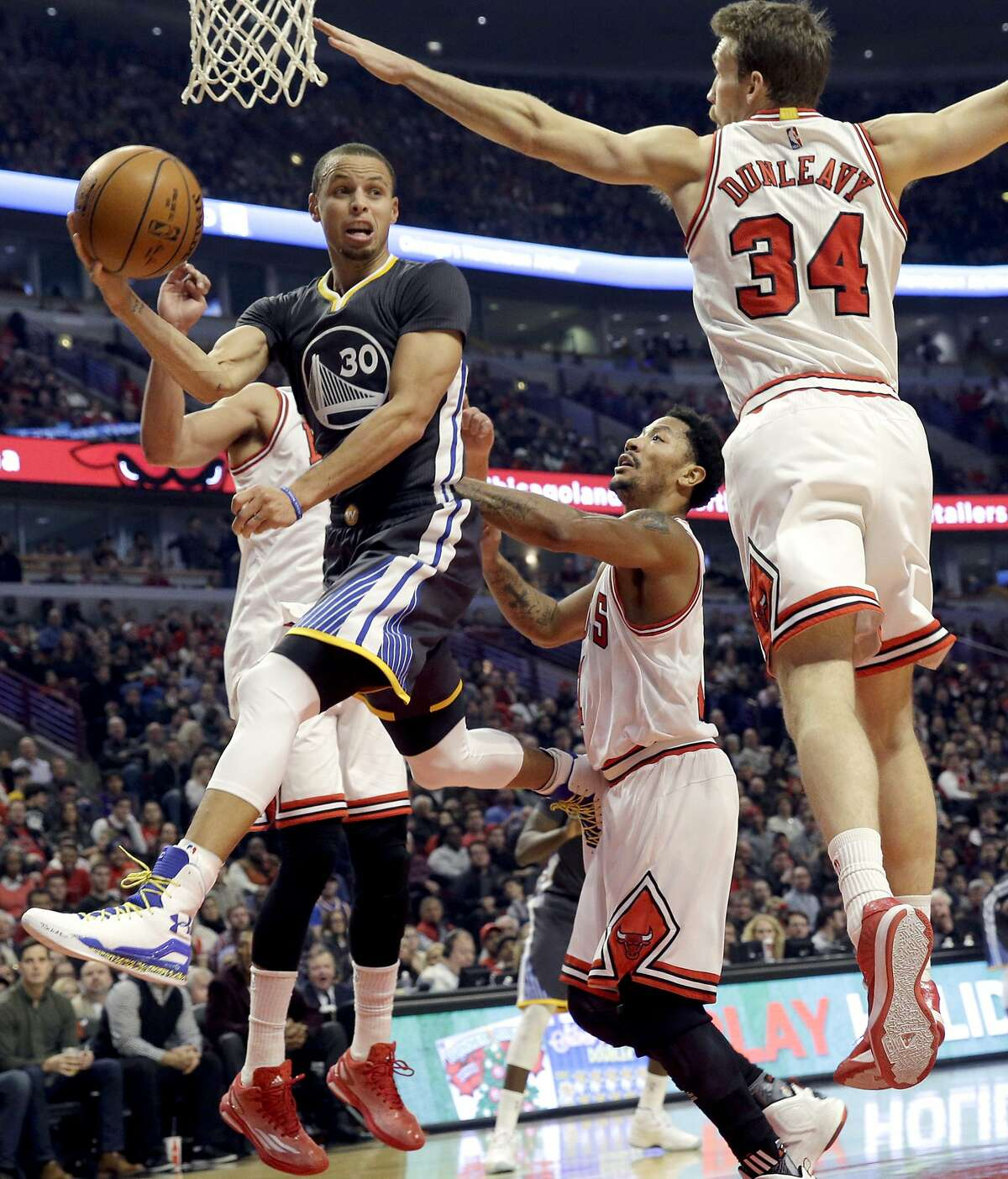 Golden State Warriors guard Stephen Curry (30) looks to pass against Chicago Bulls center/forward Joakim Noah (13), guard Derrick Rose (1) and guard/forward Mike Dunleavy (34) during the first half of an NBA basketball game in Chicago on Saturday, Dec. 6, 2014.