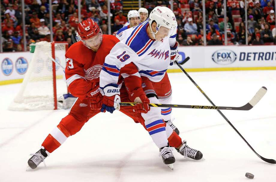 Detroit Red Wings center Darren Helm (43) and New York Rangers right wing Jesper Fast (19) battle for the puck in the second period during an NHL hockey game in Detroit, Saturday, Dec. 6, 2014. (AP Photo/Paul Sancya)   ORG XMIT: MIPS109 Photo: Paul Sancya / AP