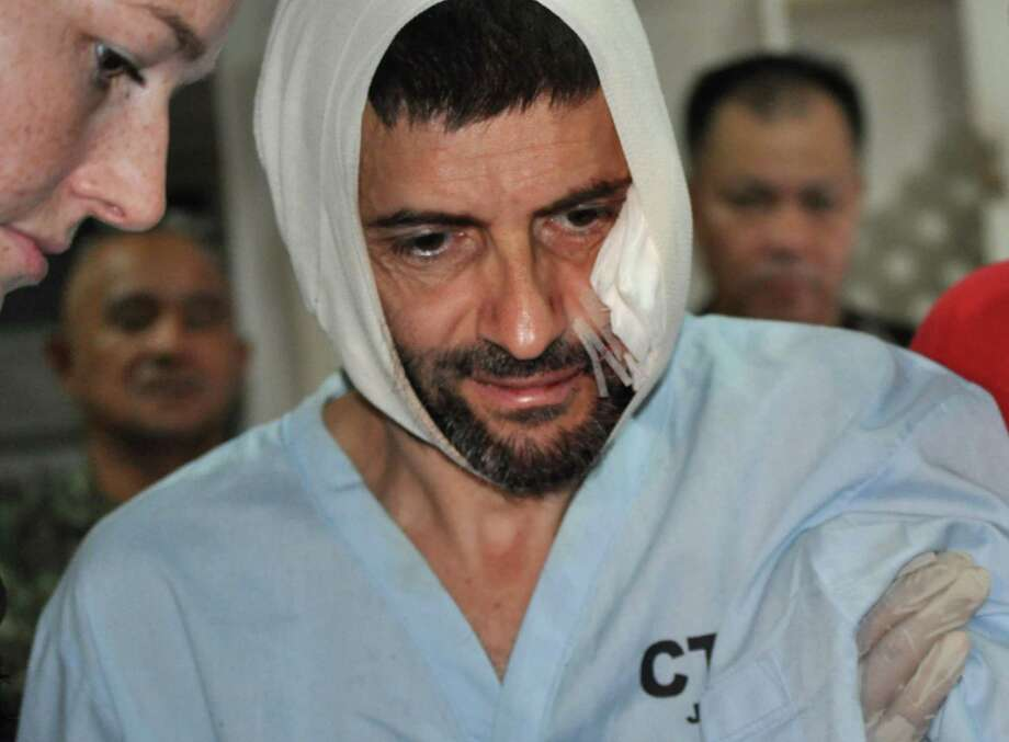 Swiss hostage Lorenzo Vinciguerra, is treated in a hospital following his daring escape from the hands of the Muslim Abu Sayyaf extremists, in Jolo in southern Philippines, Saturday, Dec. 6, 2014. Vinciguerra, who has been a hostage for two years, made a dramatic escape Saturday from Abu Sayyaf extremists when he hacked a rebel commander then got shot as he dashed to freedom amid a military artillery assault, ending more than two years of jungle captivity in the southern Philippines, officials said. (AP Photo/Nickee Butlangan) Photo: Nickee Butlangan, STR / Associated Press / AP