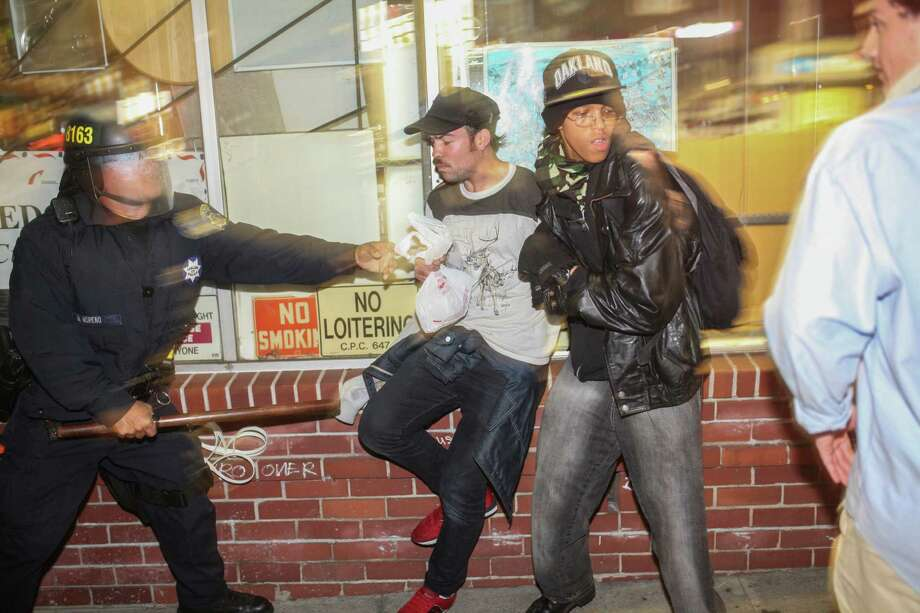 Demonstrators clash with police, in front of a man who broke his leg during the protest in Berkeley, California on Saturday, December 6, 2014. Demonstrators were responding to the grand jury verdicts in the shooting death of Michael Brown in Ferguson, Missouri and the chokehold death of Eric Garner in New York City by local police officers in their communities. Photo: Sam Wolson / Special To The Chronicle / ONLINE_YES