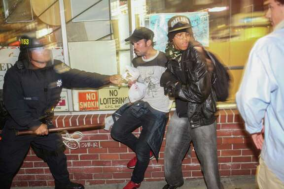 Demonstrators clash with police, in front of a man who broke his leg during the protest in Berkeley, California on Saturday, December 6, 2014. Demonstrators were responding to the grand jury verdicts in the shooting death of Michael Brown in Ferguson, Missouri and the chokehold death of Eric Garner in New York City by local police officers in their communities.