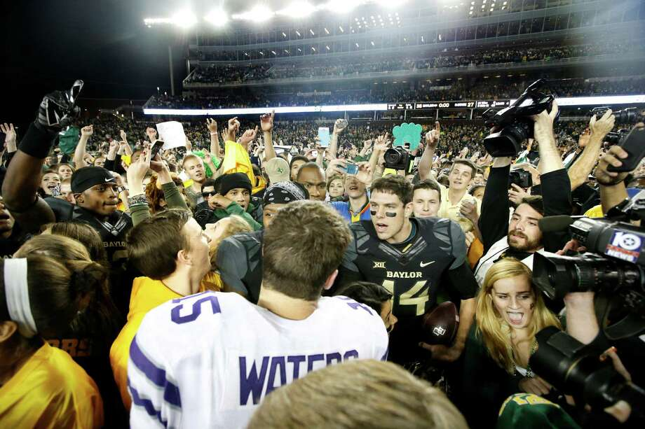 Kansas State quarterback Jake Waters (15) and Baylor quarterback Bryce Petty (14) greet each other on the field as they stand surrounded by fans that rushed the field after the 38-27 Baylor win in an NCAA college football game, Saturday, Dec. 6, 2014, in Waco, Texas. (AP Photo/Tony Gutierrez) Photo: Tony Gutierrez, STF / Associated Press / AP
